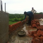 Laying bricks for the parapet around the roof of the boys dorm.