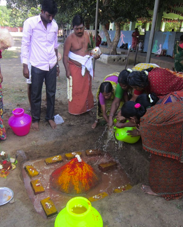 Pouring water on the bricks during the puja for the new dormitory.