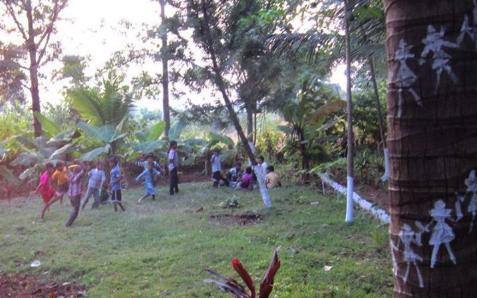Kids running around with a decorated tree trunk in the foreground.