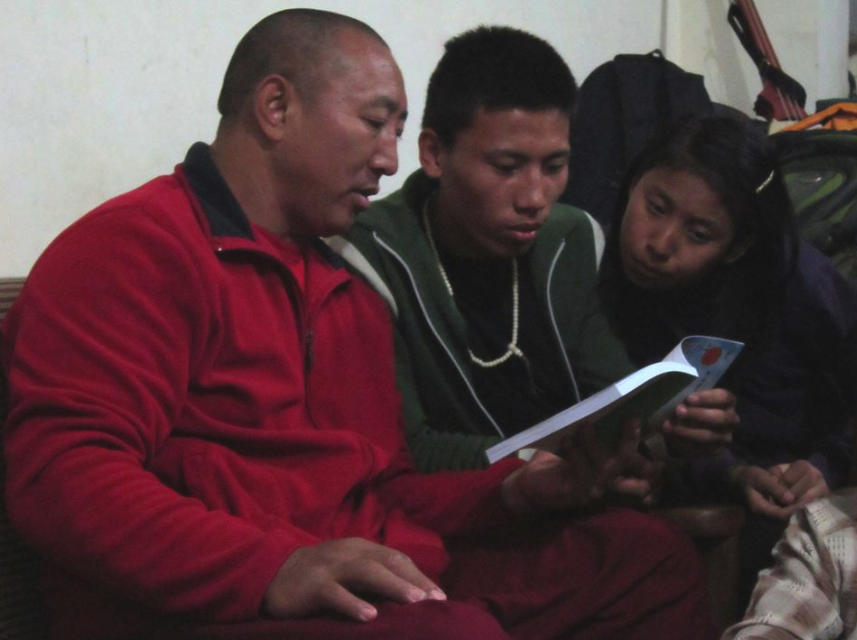 Manager Lama Tenzing helping Dhonyoun Gyalpo read a new Tibetan book from Lhasa.
