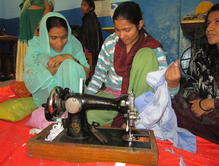 Women learning to use a hand treadle sewing machine.