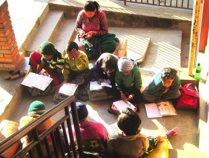 Kids at the home studying in a sunlit stairwell.