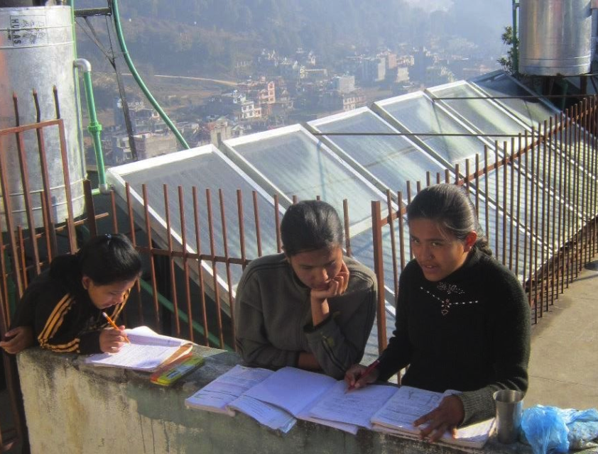 Some of the older girls studying on the roof in front of the solar hot water array. Even with so many panels, the kids are on a hot shower schedule by grade. A cold shower can be had anytime.